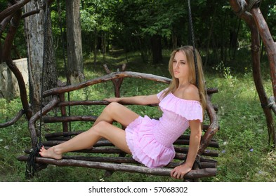 Girl in pink dress on the swing
