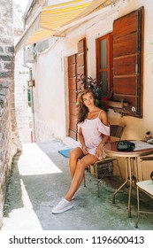 a girl in a pink dress sat down to relax from a walk through the streets of Montenegro.
