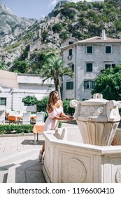 a girl in a pink dress washes her hands in the square of a European city