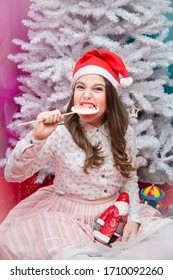 Girl in a pink elegant dress with a lollipop and Santa Claus in hands