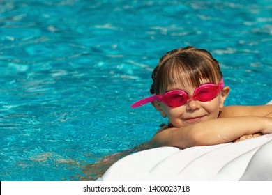Girl in pink glasses for swimming have a good time in the pool with an inflatable mattress.