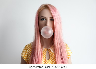 The girl with the pink hair is blowing bubble gum
