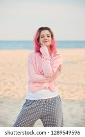 girl with pink hair in a knitted suit on the background of the sea