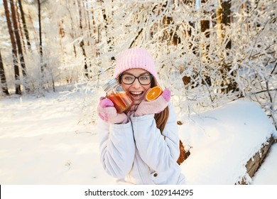 girl in a pink hat drinking mulled wine in the winter in the forest