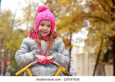 Girl in the pink hat riding on a swing fall