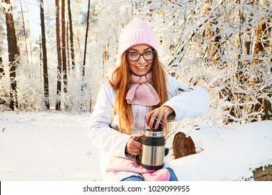 girl in a pink hat with a thermos in the winter in the forest