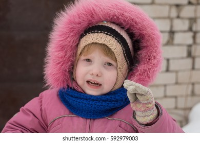 A girl in a pink jacket. Dissatisfied face. Emotions. Portrait, close-up.