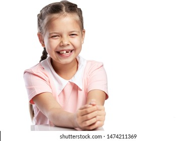 A girl in a pink jacket of a school age without a front tooth laughs. Close-up. Change of teeth. Isolated on a white background.