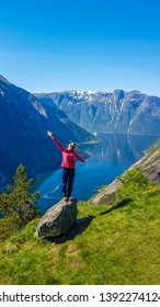 A girl in pink jacket stands on a rock with hands up in the air. Majestic view on Eidfjord from Kjeasen, Norway. Slopes are overgrown with green grass. Water has dark blue color. Freedom and happiness