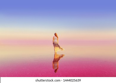 The girl in the pink lake. Unreal landscape at sunset. Between heaven and earth.