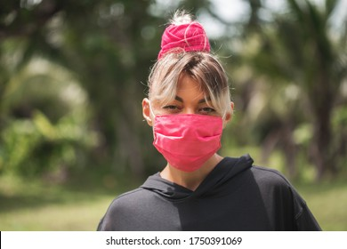 The girl in pink medical mask on nature background closeup.