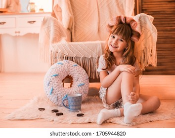 girl in pink pajamas with curlers on her head sit on the floor, beautiful little girl in pajamas on the floor,girl in pajamas at home