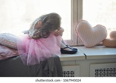 girl in pink petticoat sinng near the window