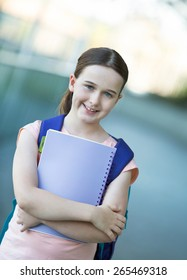 Girl in pink shirt with a purple backpack ready for the first day of school