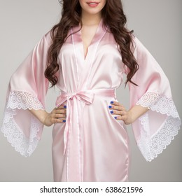 Girl in  pink silk robe, on gray background