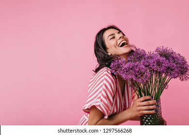 Girl in pink sundress enjoys scent of flowers and sincerely laughs, enjoying great spring day on pink background