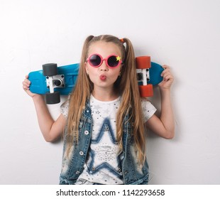A girl in pink sunglasses and a junior suit is holding a pennibord in her hands and making faces.