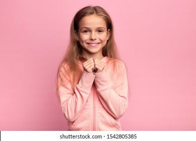 girl in pink sweater, hoody with long fair hair and clenched fists looking at the camera. sincere wish. child making a wish. belief, girl looking forward to holiday. new year