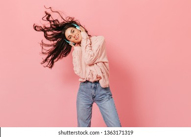 Girl in pink sweater listens to music and plays with hair. Snapshot of joyful woman on isolated background