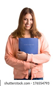 A girl in a pink sweater smiling while holding a folder.