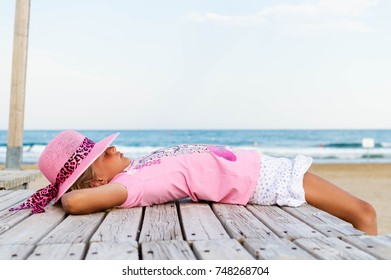 girl in pink t-shirt and pink hat is lying and relaxing on the beach on