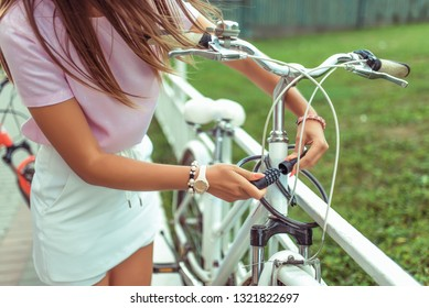 Girl in a pink T-shirt near the fence in the summer in the park. Locks, locks the cable with a code number. Protection against hijackings and scammers and thieves. Safety bike in city.