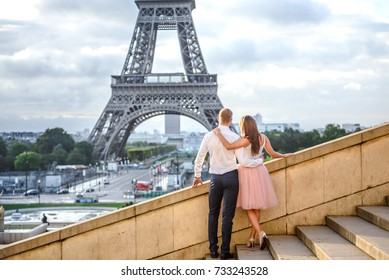 Girl in pink tutu and man in blue pants and white shirt staying at the stairs of the Trocadero place and looking at the Eiffel tower