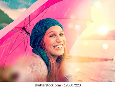 girl with pink umbrella in sunset beside a lake