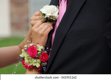 Girl pins corsage onto prom date
