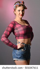 Girl in Pin-up girl style. American vintage fashion. Beautiful girl in a top and denim shorts
