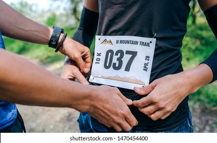 Girl placing the race number with the help of a teammate