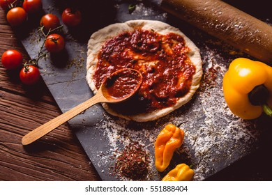 Girl is placing tomato sauce on fresh pizza