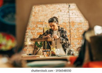 Girl in plaid shirt standing at her loft studio and making wonderful mosaic