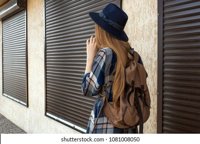 Girl in plaid shirt and vintage hat, with brown backpack.