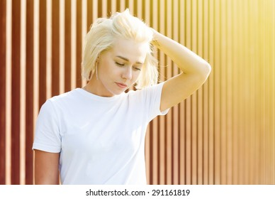Girl with platinum blond hair in white t-shirt on woden background with flare