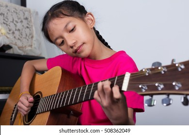 girl play acoustic guitar on music room/musician practice