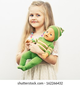 Girl play with baby doll. Mothers day concept. Isolated portrait.