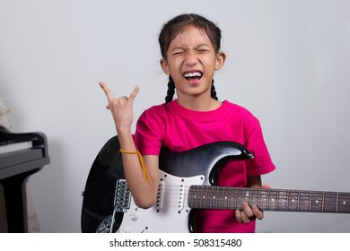 girl play electric guitar on music room/musician