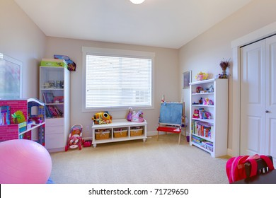 Girl play game room in white and pink with lots of toys