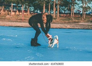 Girl play with her dog on frozen lake