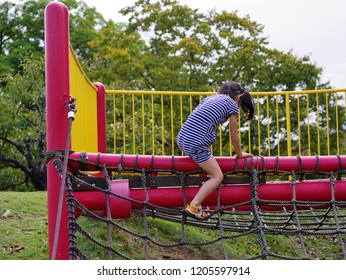 Girl playing with athletic playground equipment in park