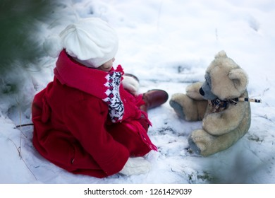 girl playing with bear in snow