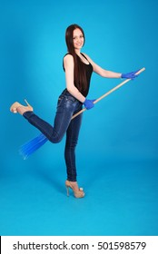Girl playing with a broom isolated on blue