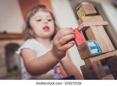 Girl playing with building blocks on floor at home