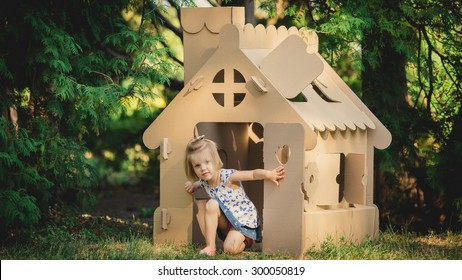 girl playing cardboard house in a city park on a sunny day