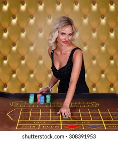 Girl playing in casino.Woman stakes piles of chips playing roulette at the casino club