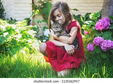 A girl is playing with a cat in her garden