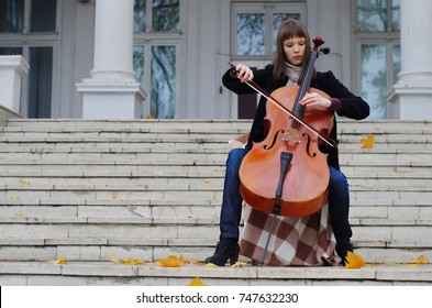 The girl is playing cello on the steps of marble staircase of an ancient house. Autumn music