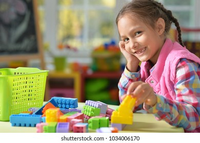 girl playing with colorful plastic blocks