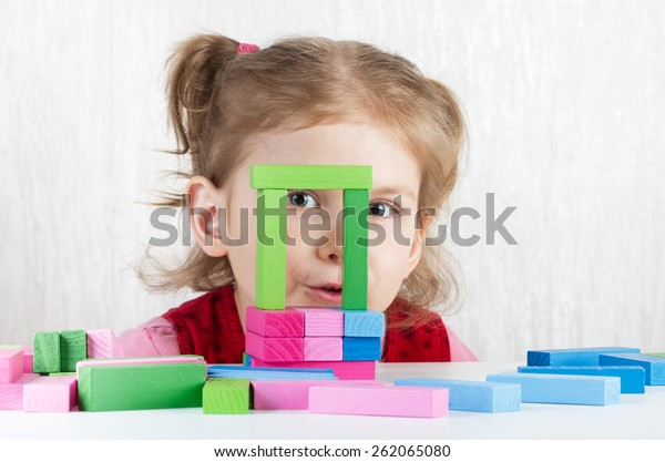 Girl playing with colorful wooden blocks